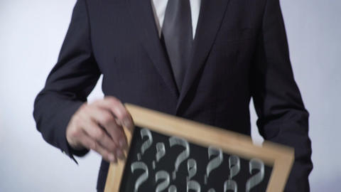 Question marks written on blackboard, male wearing classic suit holding a sign Footage