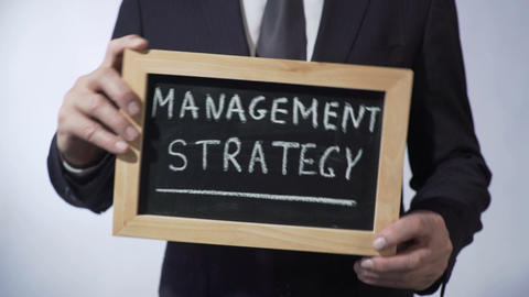 Management strategy written on blackboard, businessman holding sign, concept Footage