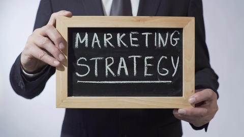 Marketing strategy written on blackboard, businessman holding sign, business Footage