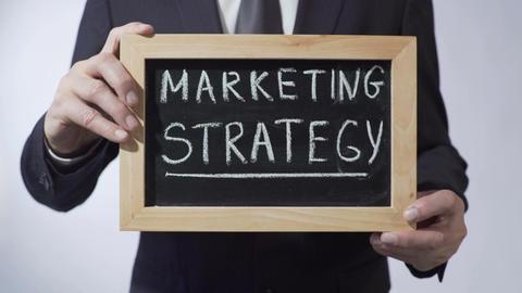 Marketing strategy written on blackboard, businessman holding sign, business Footage