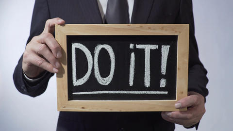 Do it with exclamation mark written on blackboard, male holding sign, motivation Footage