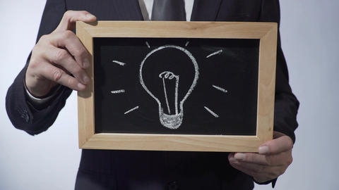 Light bulb drawing on blackboard, male in black suit holding sign, business idea Footage