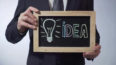 Light bulb, symbol of idea written on blackboard, man holding sign, motivation Footage