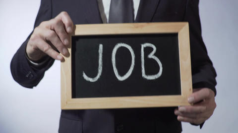 Job written on blackboard, male hands holding sign, business concept, career Footage