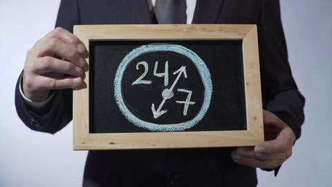 24 to 7 drawing on blackboard, businessman holding sign, business time concept Footage