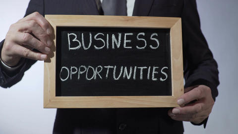 Business opportunities written on blackboard, male in suit holding sign, concept Footage
