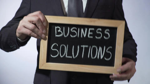 Business solutions written on blackboard, businessman holding sign, strategy Footage