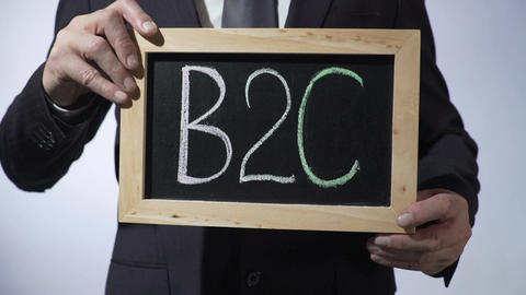 B2C, business-to-consumer written on blackboard, businessman holding sign Footage