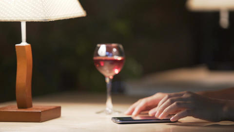 Lonely woman scrolling websites on cellphone, sipping wine at comfortable cafe Live Action