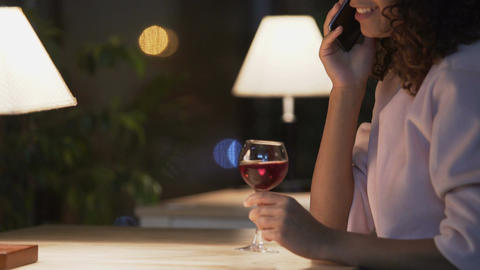 Attractive girl talking on mobile phone and drinking red wine in restaurant Footage