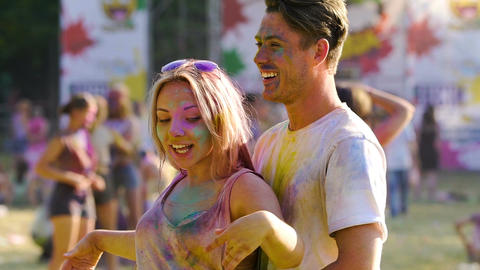 Beautiful blonde girl flirting and dancing with her boyfriend at Color festival Footage