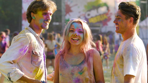 Happy friends enjoying festival of colors, dancing and spraying colored paint Footage