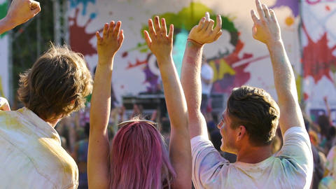 Enthusiastic youth raising hands in crowd, enjoying Holi color festival outdoors Footage