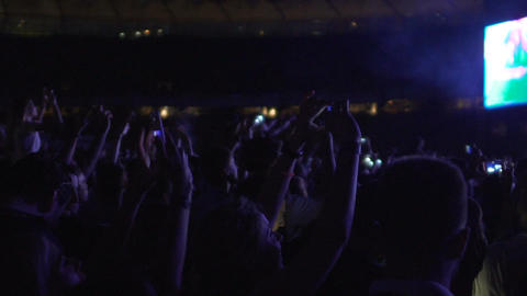 Crowd of happy people singing and dancing at concert, filming video on gadgets Footage