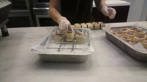 Baker putting delicious rolled cakes on tray to bake them in oven, confectionery Footage