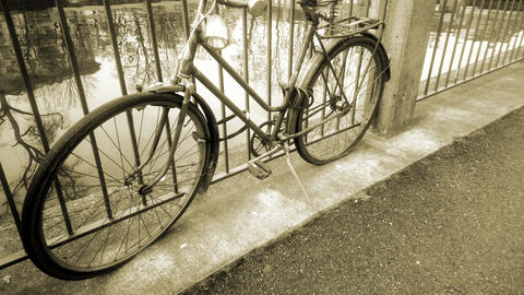 Retro bicycle standing near river tied to fence, vintage old fashioned vehicle Footage