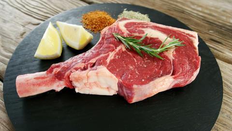 Raw steak chop and ingredients on black board Footage