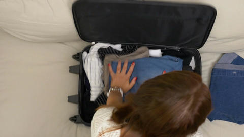 Woman packing clothes standing on her knees on overfilled suitcase trying to clo Footage