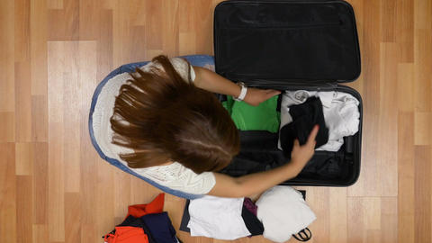 Top view of woman hurrying up to pack clothes into trolley bag and leaving to ca Footage