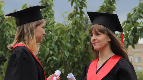 Best female friends in academic dresses holding diplomas and chatting in park Footage
