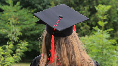 Female friends wearing graduation caps with tassels chatting near academy Footage