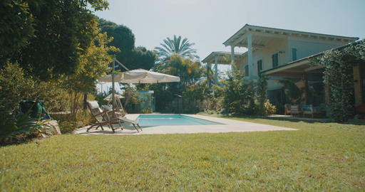 Tracking shot of a large backyard with a swimming pool in a luxurious house Live Action