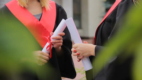 Female graduating students holding diplomas tied with red ribbons and chatting Footage