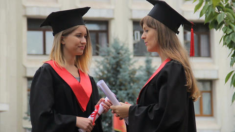 Happy smiling graduates chatting near academy and holding diplomas, conversation Footage