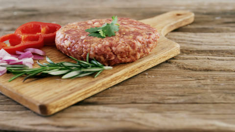 Raw hamburger patty and ingredients on wooden board Footage