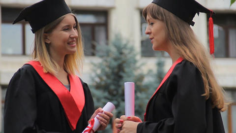 Graduates in academic dresses holding diplomas and talking after graduation Footage