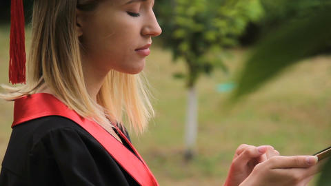 Pretty female graduate in academic cap chatting with boyfriend on smartphone Footage