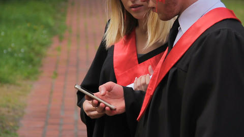 Male and female graduate students viewing photos on smartphone, graduation Footage