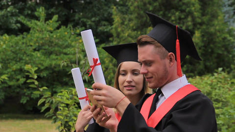 Smiling female and male graduates holding diplomas and taking selfie on phone Footage