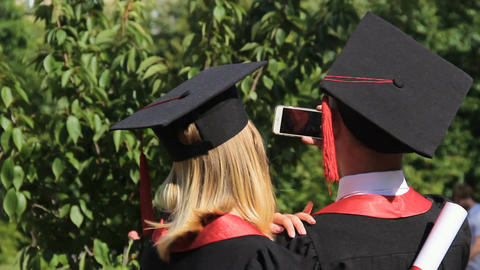 Happy pair of graduates taking selfie on smartphone in park near academy Live Action