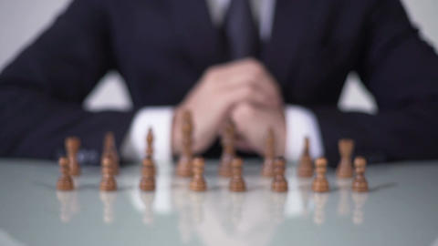 Man moving pawn in chess game, involving voters in unfair political strategy Footage