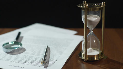 Close-up of document and hourglass on table, contract validity period expiring Footage