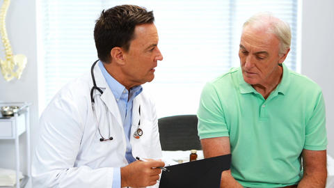 Doctor interacting with senior patient over a report Footage