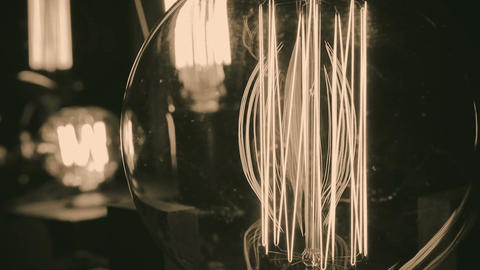 Incandescent tungsten filament trembling in light bulb, creative interior design Footage