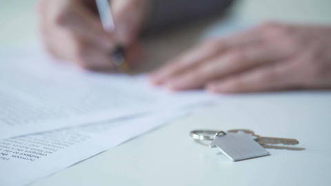 Person signing real estate purchase agreement, key from apartment on table Footage