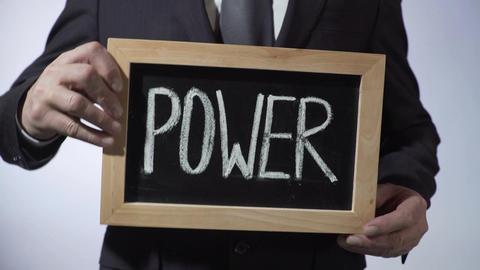 Power written on blackboard, businessman holding sign, business, politics Footage