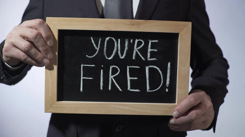 You're fired written on blackboard, businessman holding sign, business concept Footage