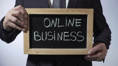 Online business written on blackboard, businessman holding sign, freelance Footage