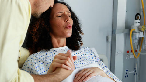 Man comforting pregnant woman during labor in ward, Live Action