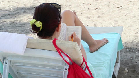 Girl Reading A Book On The Beach Filmmaterial