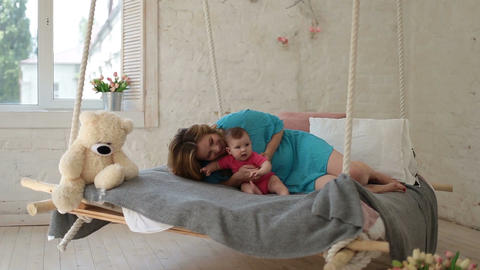Young mother playing with baby daughter in bed Filmmaterial
