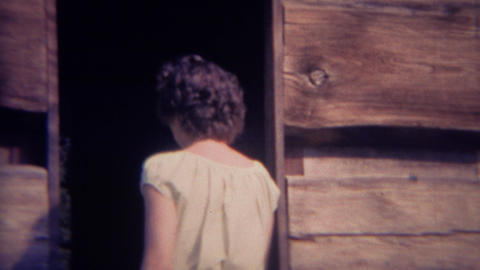 1966: Curly haired farm maiden enters wood cabin building structure Live Action
