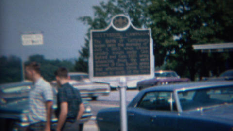1968: Family outdoor deciding at classic parked cars and historic sign Footage