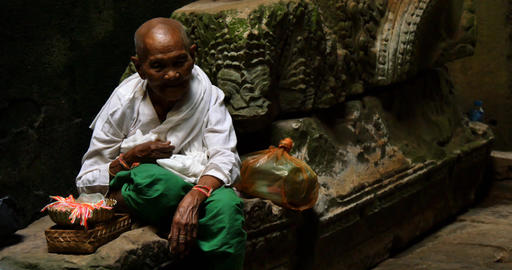 Old man Cambodian beggar monk sitting in temple offering preyer Footage