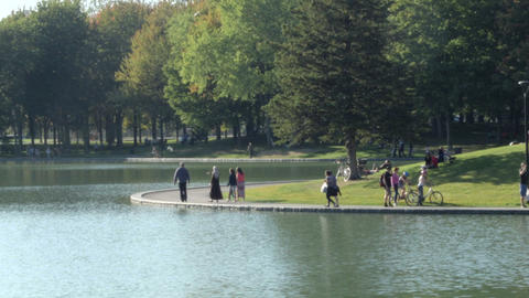 People walking around pond in a Montreal Park Footage