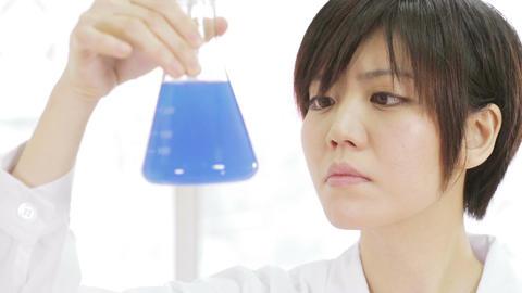 Female scientist inspects blue erlenmeyer flask Footage